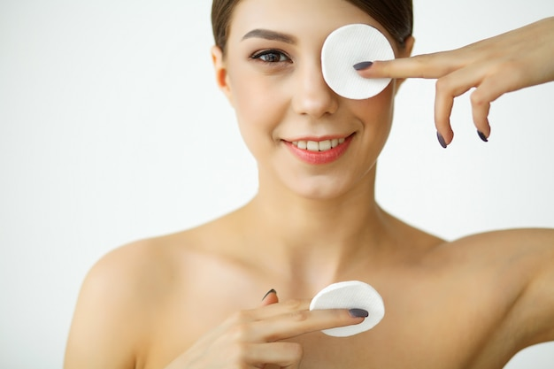 Skincare. young woman with lotion washing face at bathroom Premium Photo