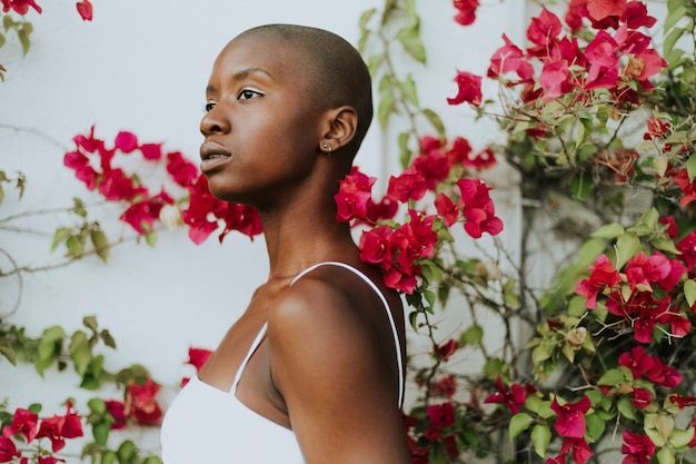 Skinhead woman surrounded by red flowers Premium Photo