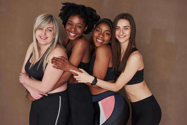 細くて大きい。茶色の空間に立っている多民族の女性のグループ Premium写真