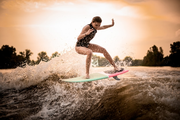 Skinny girl jumping on the wakeboard on the river on the wave in the sunset Premium Photo
