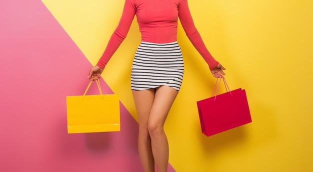 손에 쇼핑백을 들고 세련된 화려한 옷을 입은 마른 여자, 분홍색 노란색 배경, 스트라이프 미니 스커트, 판매, Discout, 쇼핑 중독, 패션 여름 트렌드, 세부 정보, 엉덩이 무료 사진