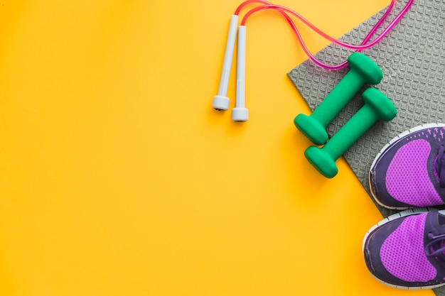 Skipping rope; dumbbells and pair of shoes with exercise mat on yellow background Free Photo