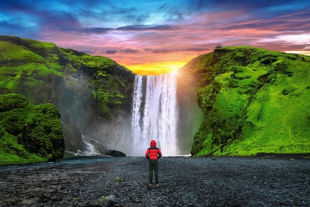 Cascata di skogafoss in islanda. ragazzo in giacca rossa guarda la cascata di skogafoss. Foto Gratuite