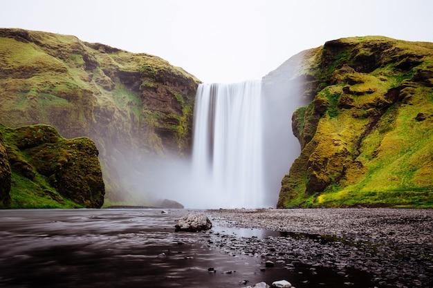 Красивый водопад между зелеными холмами в skogafoss, исландия Бесплатные Фотографии
