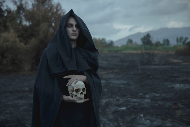 Skull being held by male mage in black clothes Free Photo