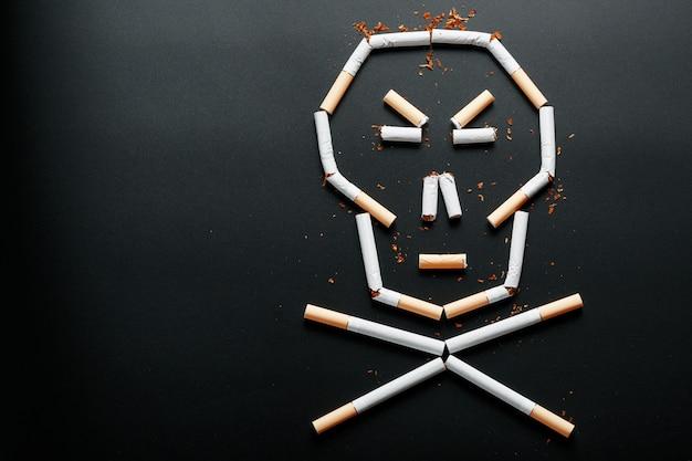 タバコの頭蓋骨。喫煙の概念は殺します。致命的な習慣としての喫煙の概念に向けて、ニコチン毒、喫煙による癌、病気、喫煙をやめます。 Premium写真