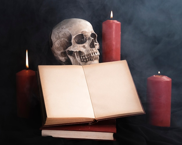 Skull with book mock-up and candles Free Photo