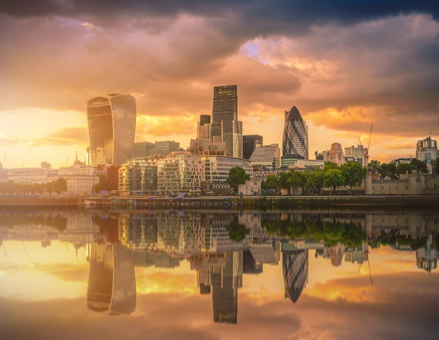 Skyscrapers of the city of london over the thames river at sunset in england. Premium Photo