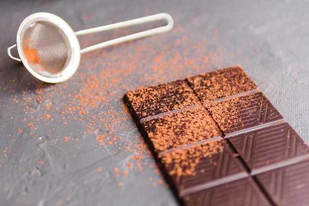 Slab of chocolate with cocoa next to strainer Free Photo