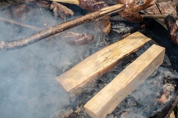 スモークラード(slanina)、ソーセージ、パンを火で調理 Premium写真