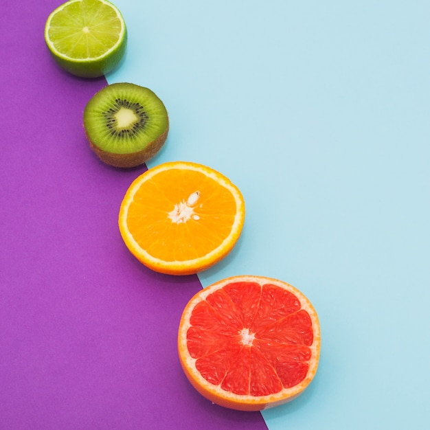 Slanting row of citrus fruits and kiwi on dual blue and purple background Free Photo