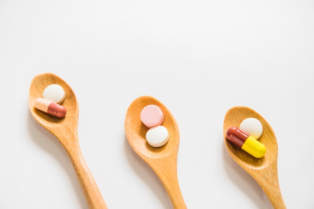Slanting wooden spoons with pills on white background Free Photo
