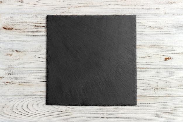 Slate board on wooden Premium Photo