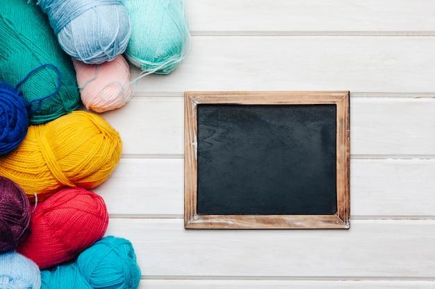 Slate next to many wool balls Free Photo