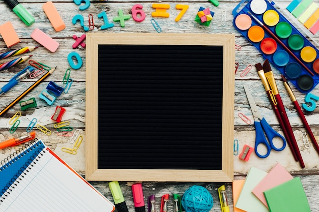 Slate with school supplies on a wooden table. Free Photo