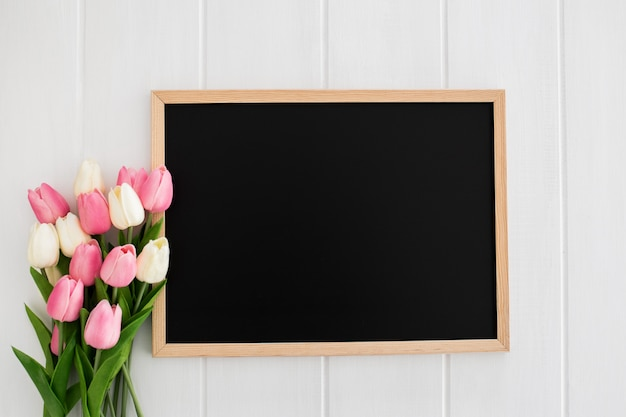 Slate with tulips on white wooden background Free Photo
