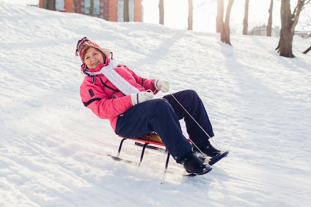 Sledding down. senior woman having fun on sleigh in winter park. winter activities Premium Photo