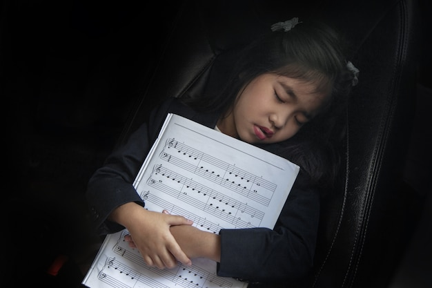 Sleep kid with music note on seat car as love music Premium Photo