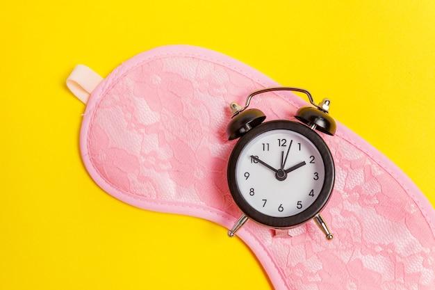 잠자는 아이 마스크, 노란색 테이블에 고립 된 알람 시계 프리미엄 사진