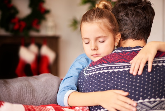 父の腕の中で眠っている女の子 無料写真