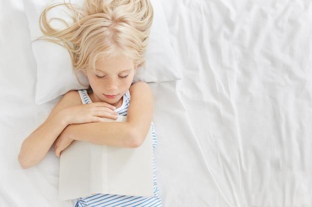 Спящая девушка с длинными светлыми волосами, держит книгу в руках, засыпает после чтения фантазий или сказок, видит приятные сны. малыш отдыхает в уютной комнате после активной игры с друзьями Бесплатные Фотографии