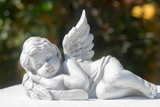 Sleeping of little cupid's ceramic doll on stone. items for house, garden, and interior Premium Photo