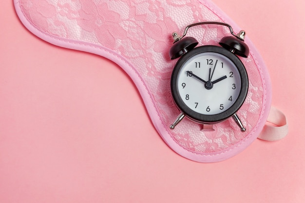 Sleeping mask and alarm clock on pink Premium Photo