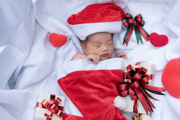 Sleeping newborn baby face in christmas hat with gift box from santa claus Premium Photo