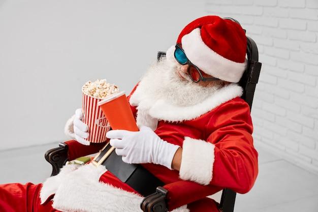 Sleeping saint nicholas in armchair with popcorn and cola Premium Photo