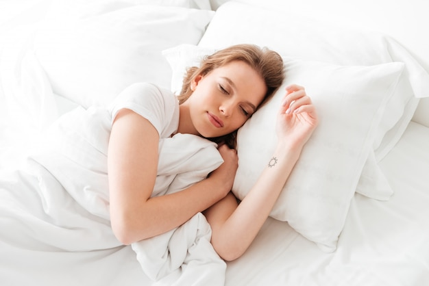 Sleeping young woman lies in bed with eyes closed. Free Photo