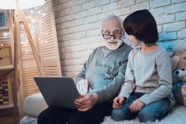 Sleepy boy sitting near working laptop grandpa Premium Photo