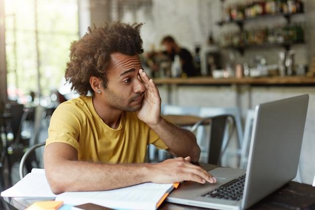 Studente universitario assonnato con i capelli folti e la pelle scura che si strofina gli occhi con la mano mentre guarda nello schermo del laptop che vuole dormire stanco preparandosi per gli esami finali. Foto Gratuite
