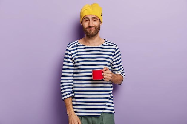 L'uomo assonnato insoddisfatto ha la routine mattutina, essendo stanco dopo una notte insonne, indossa un cappello giallo e un maglione a righe Foto Gratuite