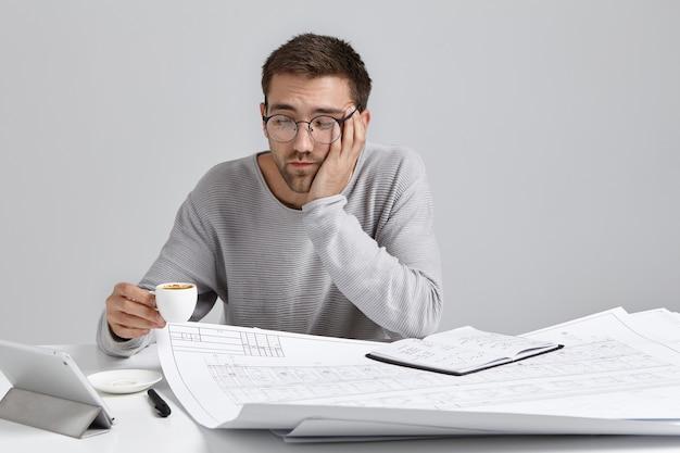 L'uomo assonnato beve caffè perché si sente stanco, lavora tutto il giorno ai progetti, ha un'espressione affaticata Foto Gratuite