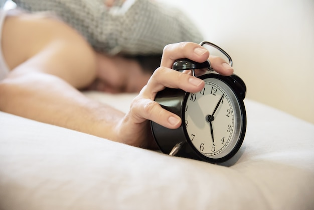 Sleepy man holding the alarm clock Free Photo
