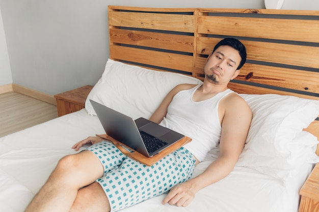 Sleepy man is working with his laptop on his cozy bed. concept of boring freelancer lifestyle. Premium Photo