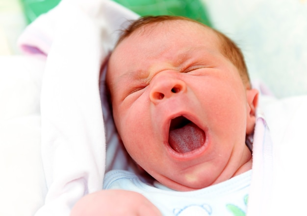Sleepy new born baby yawning with his mouth open Premium Photo