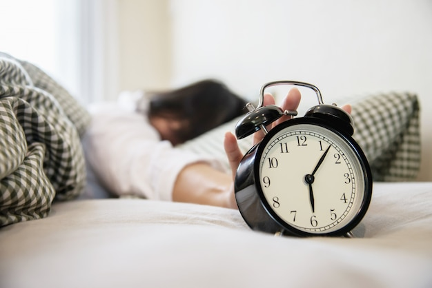 Sleepy woman reaching holding the alarm clock Free Photo