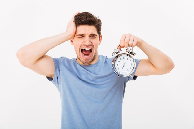 Sleepy young man 30s with brown hair holding alarm clock and yawning in morning, isolated over white wall Premium Photo
