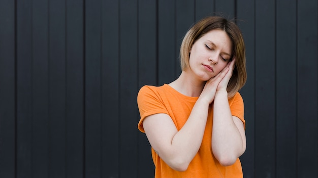 Sleepy young woman standing against black backdrop Free Photo