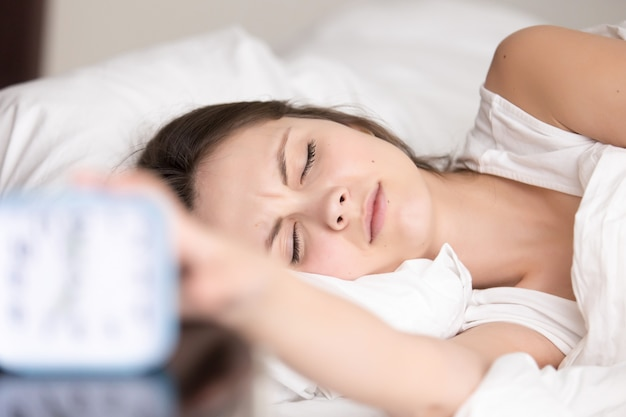 Sleepy young woman turns off signal of alarm clock Free Photo