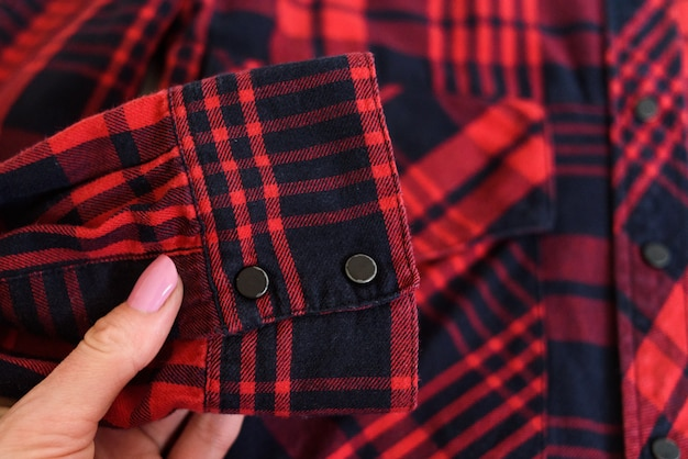 Sleeve of a red checkered shirt in a female hand. close-up. fashion . Premium Photo