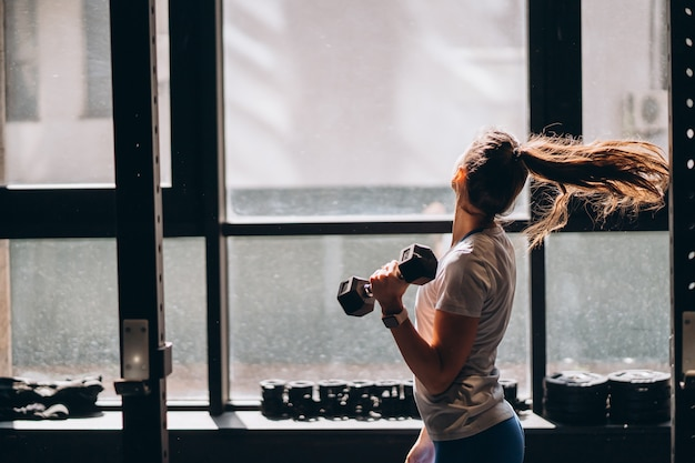 Slender athletic girl performs physical exercises with dumbbells. Free Photo