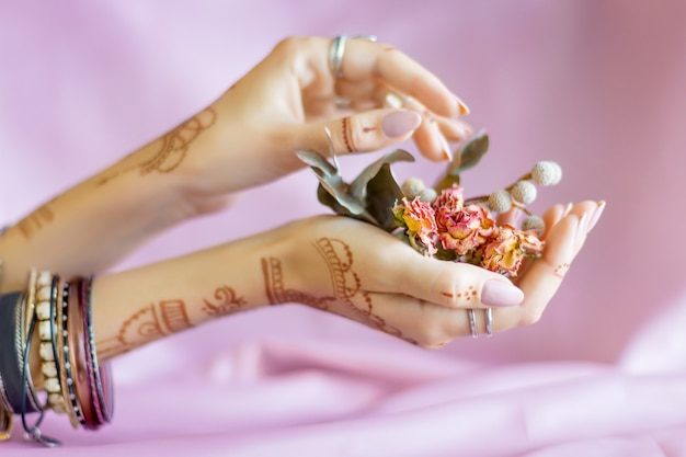 Slender elegant female wrists painted with traditional indian oriental mehndi ornaments by henna. hands dressed in bracelets and rings hold dry roses flowers. pink fabric with folds on background. Premium Photo