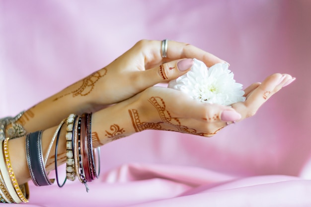 Slender elegant female wrists painted with traditional indian oriental mehndi ornaments by henna. hands dressed in bracelets and rings hold white flower. light pink fabric with folds on background. Premium Photo