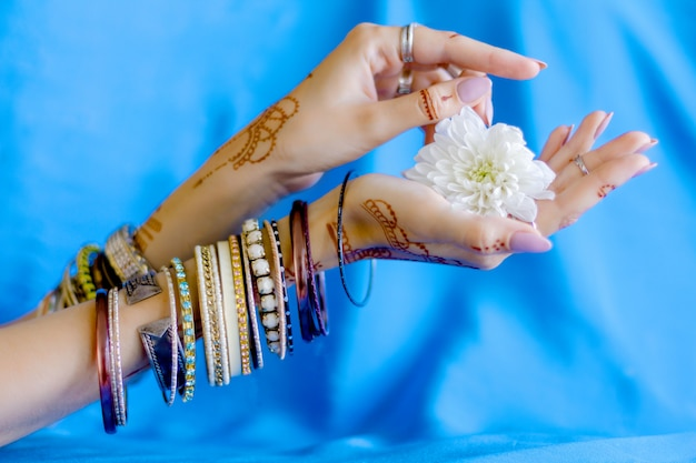 Slender elegant female wrists painted with traditional indian oriental mehndi ornaments by henna. hands dressed in bracelets and rings hold white flower. sky blue fabric with folds on background. Premium Photo