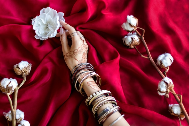 Slender female hand painted with indian oriental mehndi ornaments by henna. hand dressed in bracelets hold white flower. maroon color fabric with folds and cotton branches on background. Premium Photo