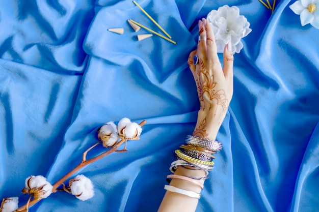 Slender female hand painted with indian oriental mehndi ornaments by henna. hand dressed in bracelets and rings hold white flower. blue fabric with folds and cotton branches on background. Premium Photo