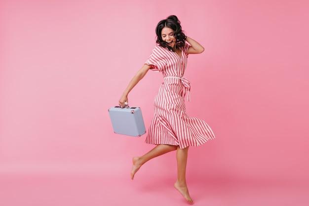 멋진 분위기의 날씬한 소녀는 재미 있고 손에 가방을 들고 춤을 추고 있습니다. 랩 드레스에서 이탈리아 모델의 샷입니다. 무료 사진
