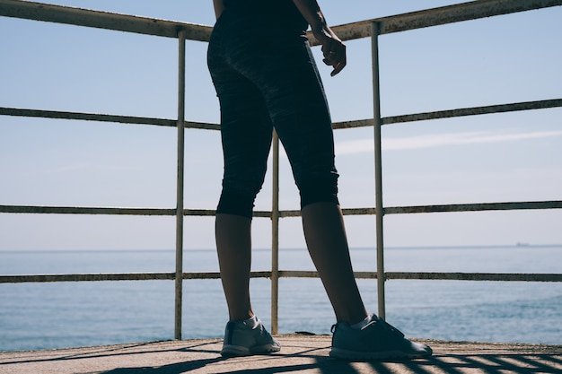 Slender women's legs in blue sneakers and athletic pants against the of the sea in the early morning Premium Photo